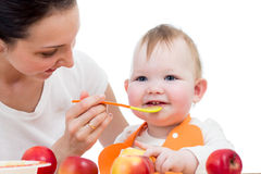 Young mother spoon-feeding her baby girl royalty free stock photography