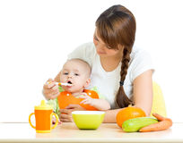 Young mother spoon feeding her baby girl at desk