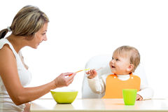 Young mother spoon feeding her cute baby Royalty Free Stock Image
