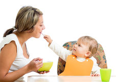 Young mother spoon feeding her playful child girl Royalty Free Stock Photo