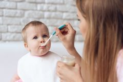 Young mother with spoon feeding little baby. stock image