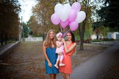 Young mother standing with sister and little baby, keeping balloons. Young mother standing with sister and little daughter, keeping balloons. Concept of royalty free stock photography