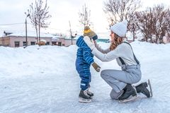 A young mother straightens her son`s cap boy. In winter in city on the ice rink. In winter clothes skating, on a. A young mother straightens her son`s cap boy stock photo