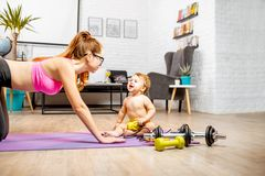 Mother exercising with her baby son at home. Young mother stretching on the mat with her baby son playing on the floor at home stock image