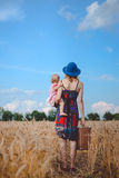 Young mother in sundress and hat with child and. Young mother in bright sundress and blue hat carrying her child and retro suitcase walking away across field of Stock Images