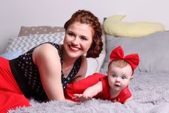 Young mother and surprised baby in red bow are on bed. With pillows in bedroom Stock Photos