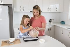 Young mother and sweet little daughter baking together happy at home kitchen in family lifestyle concept Royalty Free Stock Photography