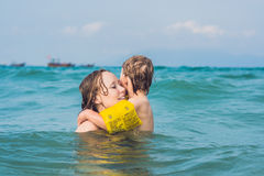 Young mother swimming and playing with male child boy in sea or ocean water sunny day outdoor on natural background, horizontal pi Royalty Free Stock Image