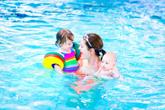 Young mother in swimming pool with two kids. Young mother having fun in a swimming pool with a toddler girl aan newborn son Stock Photo