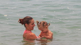 Young mother swims play with little daughter in shallow sea stock footage