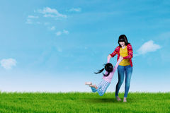 Young mother swings her daughter on meadow. Young mother swings her daughter on the meadow while playing under the blue sky Royalty Free Stock Image