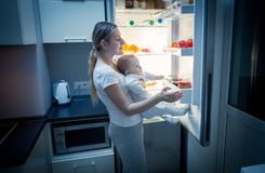 Young mother taking food out of refrigerator at night to cook something for her hungry baby Royalty Free Stock Image