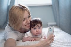 Young mother taking selfie with her cute baby on bed royalty free stock photos