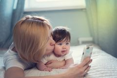 Young mother taking selfie with her cute baby on bed stock photos