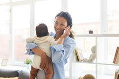 Young mother talking on phone while holding baby stock photography