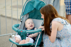 Young mother talking to her baby in a stroller Royalty Free Stock Photo