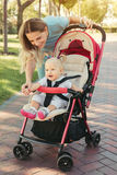 Young mother talking to smiling baby in pink stroller. Parents w. Alking outdoors with child in summer pram stock photos