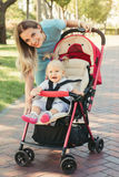 Young mother talking to smiling baby in pink stroller. Parents w. Alking outdoors with child in summer pram royalty free stock images
