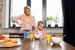 Young mother talking with upset little daughter sitting at table. At breakfast stock images