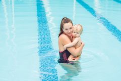 Young mother teach her little son, how to swim in a swimming pool.  Royalty Free Stock Photos