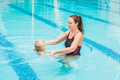Young mother teach her little son, how to swim in a swimming pool.  royalty free stock photography
