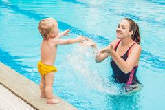 Young mother teach her little son, how to swim in a swimming pool.  stock image