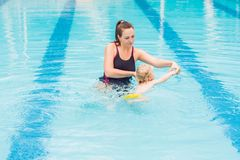 Young mother teach her little son, how to swim in a swimming pool stock photo