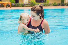 Young mother teach her little son, how to swim in a swimming pool stock image
