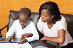 Schoolboy studying with his mother. Young mother teaches her child at home royalty free stock photography