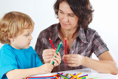 Young mother teaches her child to draw with color pencils Royalty Free Stock Images