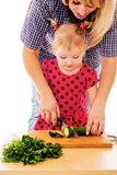 Young mother teaches her daughter. To cut vegetables in the kitchen- isolated on white background Royalty Free Stock Image