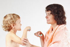 Young mother teaches her son to brush their teeth Stock Image