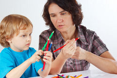 Young mother teaches her son to draw with pencils Royalty Free Stock Images