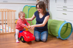 Young mother is teaching her child to drive toy car. Woman is playing with daughter Royalty Free Stock Images