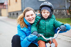 Young mother teaching her 2 years old little son to ride a bike, Royalty Free Stock Images
