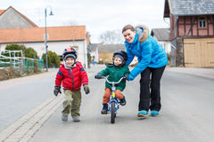 Young mother teaching her 2 years old little son to ride a bike Stock Image