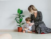 Young mother teaching a little toddler boy care with plant royalty free stock photography