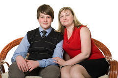 Young mother and teenage son on sofa Stock Photo