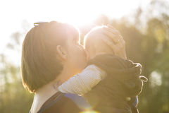 Young Mother Tenderly  Lifting and Kissing her Baby Boy. Backlit by Bright Sunlight Outdoors in Family, Love and Togetherness Themed Image Stock Image