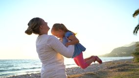 Young mother throwing daughter in the air. At the beach, slow motion stock video footage