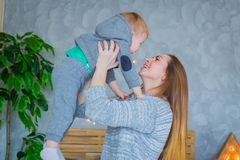 Young mother throwing up her baby son royalty free stock photo