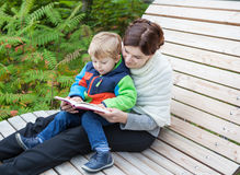 Young mother and toddler reading book outdoor Royalty Free Stock Images