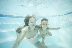 Young mother and toddler son swimming underwater in pool and having fun Royalty Free Stock Photos