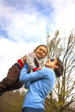 A young mother tosses the baby up. Royalty Free Stock Photography