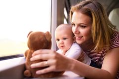 Young mother travelling with baby by train. Royalty Free Stock Images