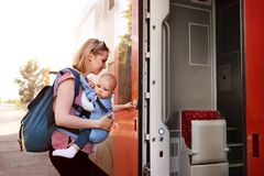 Young mother travelling with baby by train. Stock Photo