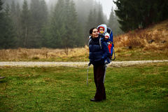 Young mother trekking, carrying her baby in a baby backpack Royalty Free Stock Photo