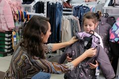 Young mother tries on children`s clothes for autumn. Preparing for the winter season with a child. Buy a warm jacket for girls. royalty free stock photo