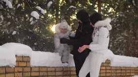 Young mother trying to cheer up his little child, who is backed by the pope, To the fell. Woman throws snow up, and then stock video footage