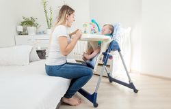 Young mother trying to feed her crying baby sitting in highchair. Young mother trying to feed crying baby sitting in highchai Stock Photography